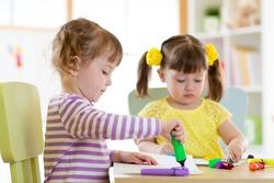 Two beautiful children girls drawing in kindergarten or preschool