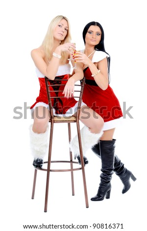 Two beautiful christmas girls in Santa Claus costume hugging in front of the wall