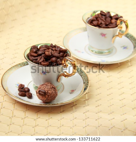 Two beautiful coffee cups with coffee beans and dessert on a beige tablecloth on food and Drink