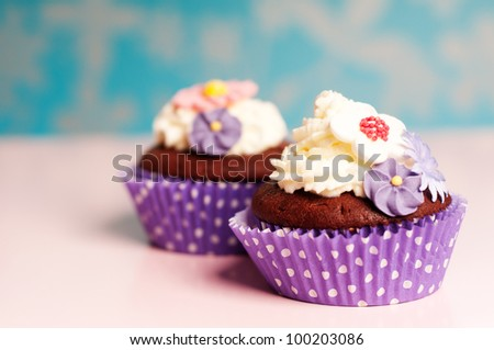 two beautiful cupcakes on a pink table with flower decoration on top