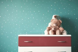 two beautiful cute teddy bear toy on the night table in turquoise room