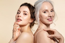 Two beautiful different age woman with perfect skin headshot portrait. Senior lady and young girl in underwear standing back-to-back posing for camera. Spa beauty salon procedure and home skincare