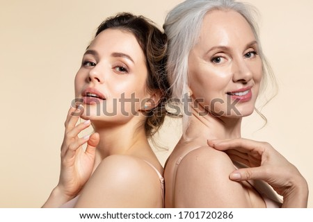 Two beautiful different age woman with perfect skin headshot portrait. Senior lady and young girl in underwear standing back-to-back posing for camera. Spa beauty salon procedure and home skincare Stock fotó ©