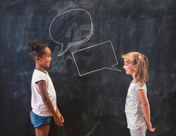 Two beautiful elementary school girls standing in front of a chalkboard in classroom, having a discussion and debate