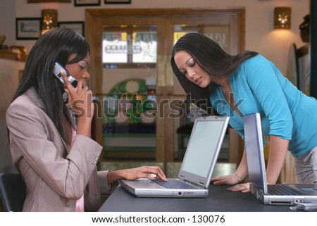 Two beautiful ethnic women working together with laptops at a restaurant table.