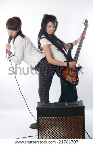 Two beautiful expressive women with microphone and guitar - stock photo