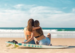 Two beautiful female friends at the beach sitting on the sand close to her surfboards embracing each other
