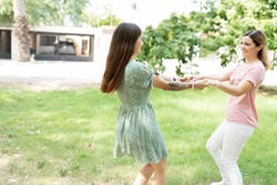 Two beautiful friends holding hands and twirling in a green grass at the park