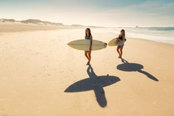 Two beautiful friends holding their surfboards and walking on the beach