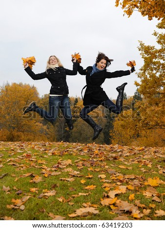 two beautiful girl friends with autumn leafs in a park jumping #63419203