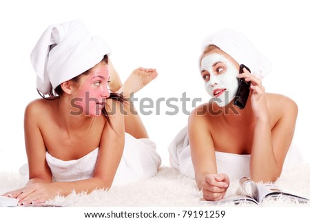 Two beautiful girl relaxing in spa with nutrient facial masks