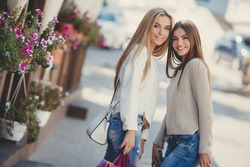 Two beautiful girlfriends with with Shopping Bags. Two women enjoy shopping. Portrait of two friends shopping together. shopping bags