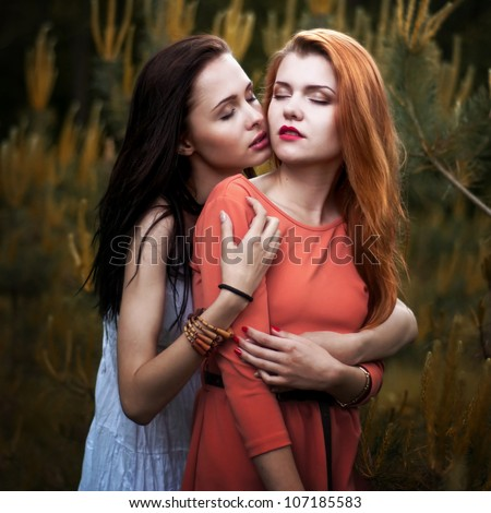 Two beautiful girls hugging each other outdoors
