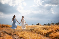 Two beautiful girls in dresses in autumn field have fun