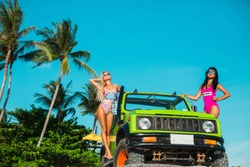 two beautiful girls in swimsuits and sunglasses travel on an off-road car, an old jeep on a tropical island, a summer trip, a fashionable photo, palms