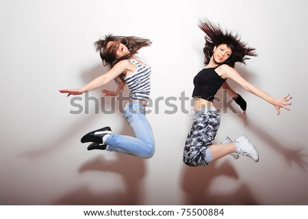 Two beautiful girls jumping against wall