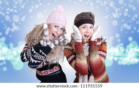 Two beautiful girls laughed in warm winter clothes over light purple background with snowflakes