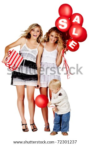 two beautiful girls laughing with red balloons with sign sale and gift box and little boy playing next to them.