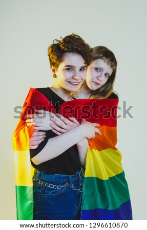 Two beautiful girls lesbians wrapped in a rainbow flag and stand on a white background #1296610870