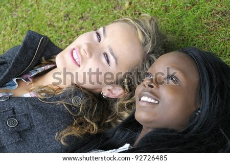 Two beautiful girls lying down. Girl on the left is slightly out of focus to enhance that dreamy look.