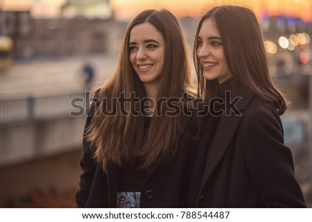 Two beautiful girls on the street having a small chat, enjoying a walk in the city