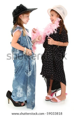 Two beautiful girls playing dress up in baggy dresses and hats over white.