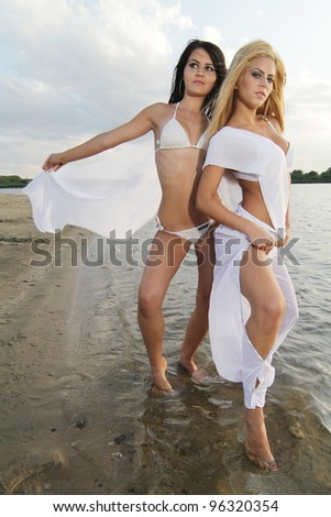 Two beautiful girls posing in the warm water at sunset