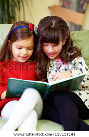two beautiful girls reading book at home