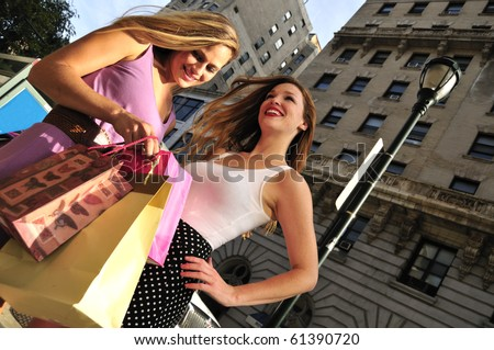 two beautiful girls shopping together in the city street