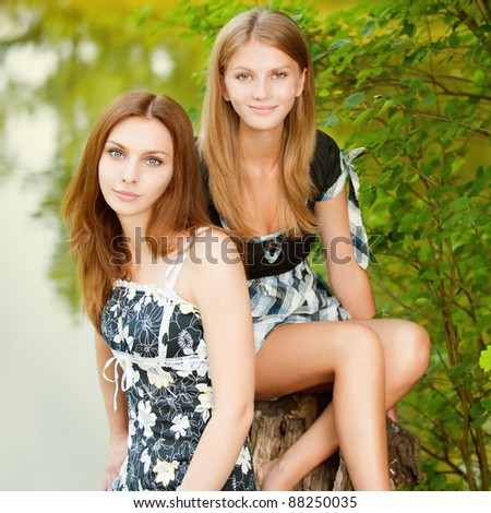 Two beautiful girls sit on stub about pond in summer city park.