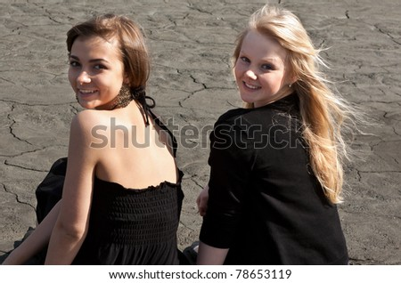 Two beautiful girls sitting on a dry log on the background of cracked earth