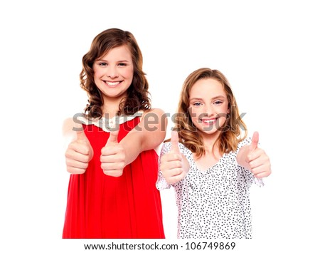 Two beautiful girls smiling and showing thumbs up at camera