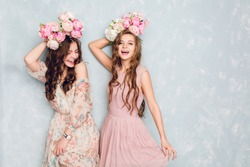 Two beautiful girls stand in a studio, play silly and have circlets of flowers on their heads. They wear light silk dresses. One is blond, and one is brunette. Both have curly hair.