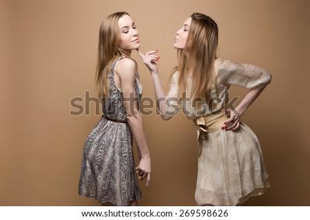two beautiful girls twins in the studio, sisters, flirt,