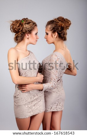 Two beautiful girls twins, isolated on the grey background - stock photo