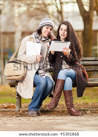 Two beautiful girls using a tablet pc outdoors