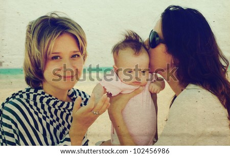 two beautiful girls with a baby on the beach. Photo in old color image style. - stock photo