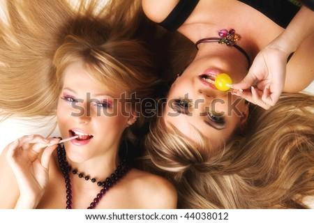Two beautiful girls with bright makeup licking lollipops