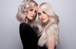 Two beautiful girls with hair coloring in blond. Stylish hairstyle curls done in a beauty salon. Beauty, cosmetics and makeup