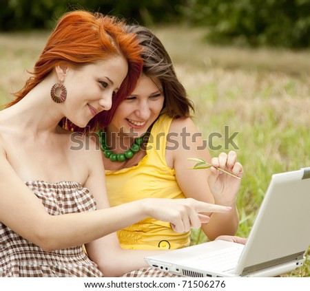 Two beautiful girls with notebook on field