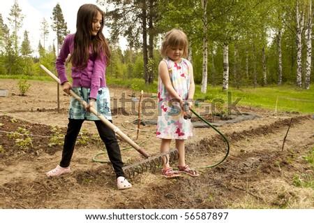 Two beautiful girs helping in the garden - stock photo
