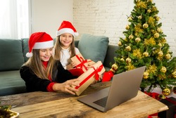 Two Beautiful happy children with computer video calling family and showing christmas presents online. Virtual Holidays celebration due to COVID-19 quarantine, stay home order and social distancing.