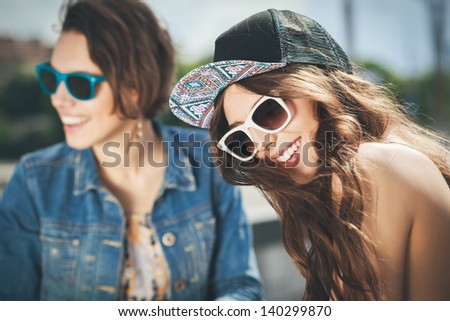 Shutterstock Two beautiful happy girls in sunglasses on the urban background. Young active people. Outdoors