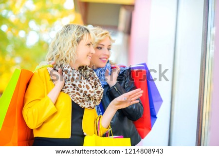 two beautiful happy girls with shopping bags show hand and look at the shop window