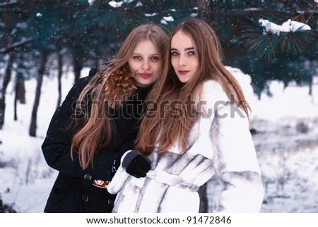 two beautiful  happy smiling girl in winter forest