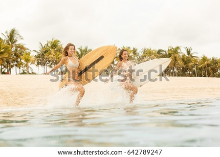 Stock Photo Two beautiful happy surfing girl running into the sea waves with lot of sparks with big shortboard surf surfboard board on sunrise or sunset. Modern active sport lifestyle and summer vacation.