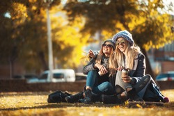 Two beautiful happy women sitting in autumn park on grass drinking coffee and laughing. Concept friendship, togetherness, happiness. Having fun on coffee break  with best friend.