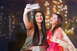 Two beautiful Indian woman taking selfie while wearing ethnic traditional clothes for Diwali or another festival celebration