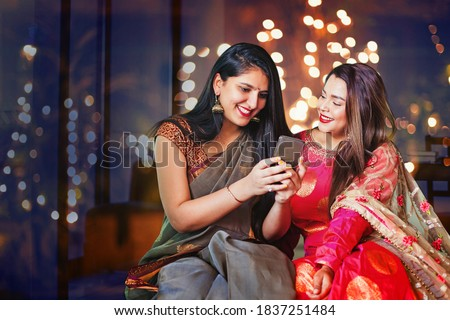 Two beautiful Indian women in ethnic clothes doing Diwali shopping online, using app on mobile phone