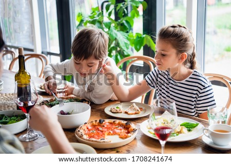 Two beautiful kids eating with a appetite